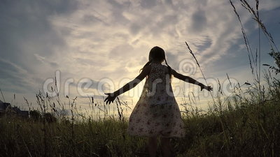 One little girl dancing in the field at the sunset time. Kid having fun outdoors. Concept of happy life stock video footage
