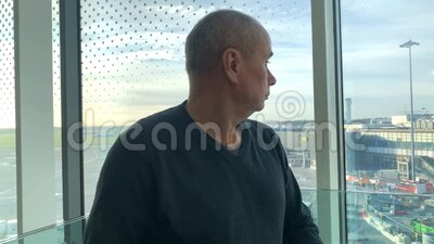 One man in a bright building of an airport lounge waiting at the window and looking at the street, travel concept stock video footage