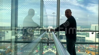 One man in a bright building of an airport lounge waiting at the window and looking at the street, travel concept stock video