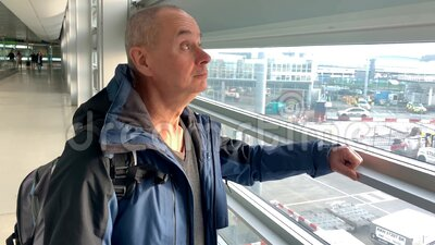 One man in a bright building of an airport lounge waiting at the window and looking at the street, travel concept stock footage