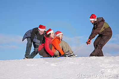 One man pull two girls on sled