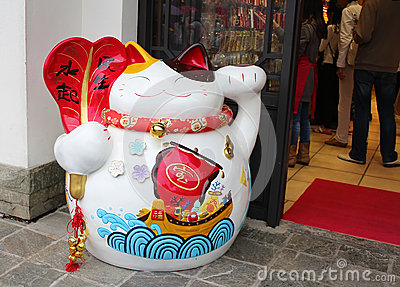 One maneki-neko (or lucky) japanese cat in front of one souvenir shop in Hong Kong Editorial Image