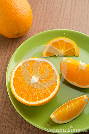 One orange and slices of orange on plate