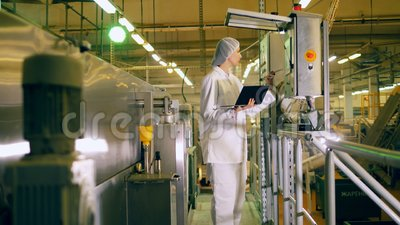 One person works with factory equipment in a food production facility. 4K stock video