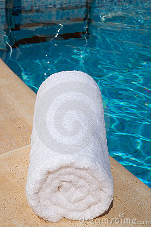 One rolled-up white towel by blue pool