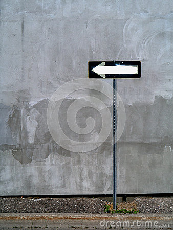 One Way sign against wall backdrop