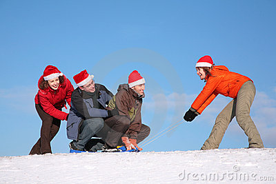 One woman pull two men on sled