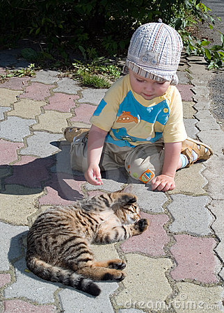 One year boy playing with cat