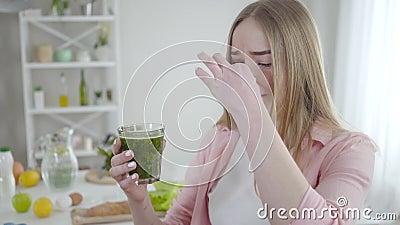 Ongelukkig Kaukasisch meisje dat zijn neus sluit met vingers om groene, gezonde cocktail te drinken Portret van havermout jonge h stock footage