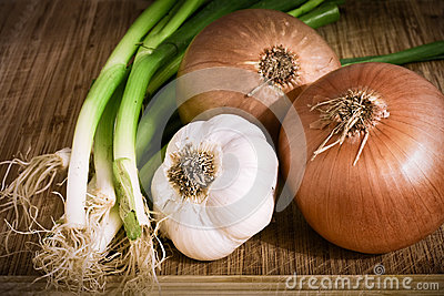 Onions, garlic on a chopping board