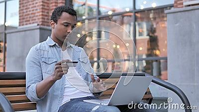 Online zakupy niepowodzenie dla Afrykańskiego mężczyzny obsiadania na ławce zdjęcie wideo