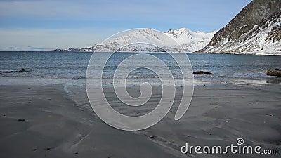Ontruim koudegolven die lichtbruine zandige kust in de recente herfst met majestueuze sneeuwbergachtergrond raken stock videobeelden