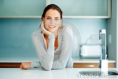 Ontspannen jonge vrouw die zich bij de keuken bevindt