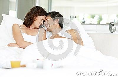Ontspannen paar dat op bed met ontbijt ligt