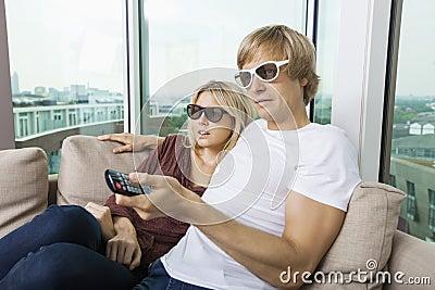 Ontspannen paar die 3D glazen thuis dragen en op TV letten