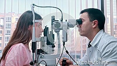 Oogheelkundige behandeling - een arts controleert de gezichtsscherpte van jonge vrouwen met een speciale apparatuur die het licht stock video