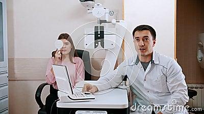 Oogheelkundige behandeling - jonge vrouw controleert haar gezichtsscherpte in de kast van de dokter stock footage
