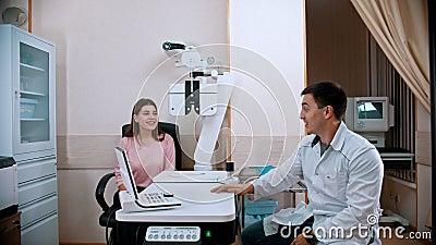 Oogheelkundige behandeling - jonge vrouw die haar gezichtsscherpte op een optometrische apparatuur controleert - het apparaat weg stock video
