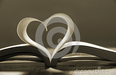 Open book with pages forming heart shape .
