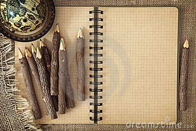 Open exercise book with pencils