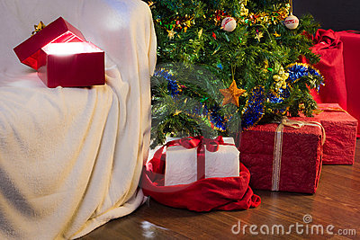 Open gift with light on christmas tree and gifts