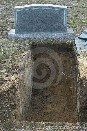 Open grave and tombstone