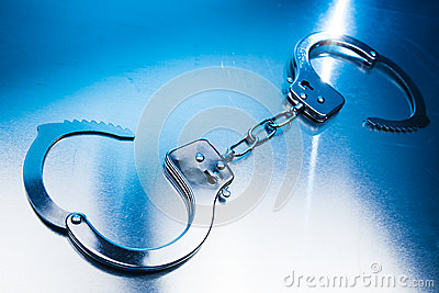 Open Handcuffs on a metallic background with dramatic lighting