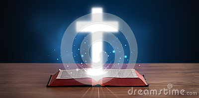 Open holy bible with glowing cross in the middle Stock Photo
