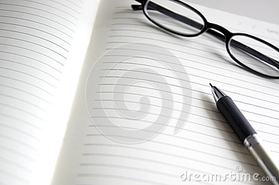 Open notebook with pen and glasses