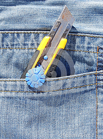 Open pocket knife in blue jeans