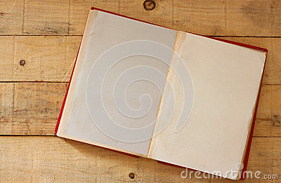 Open vintage old book on wooden table