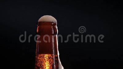 Open wet beer bottle isolated on black.  stock footage
