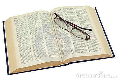Open yellowed old book with glasses