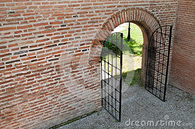 Opened iron forged gate with brick wall