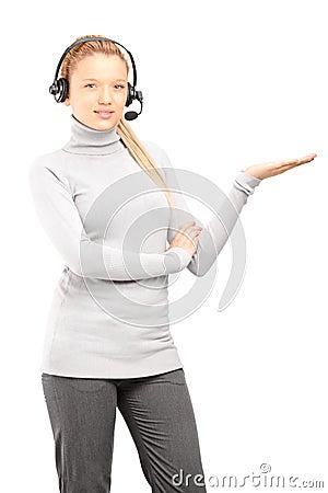 Operador de sexo femenino del servicio de atención al cliente con gesticular de los auriculares