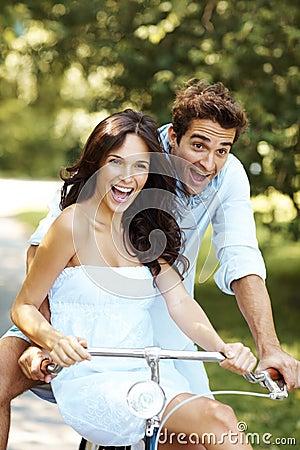 Opgewekt jong liefdepaar dat een fiets berijdt