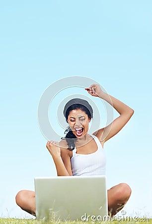 Opgewekte vrouw op gras met laptop