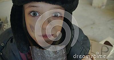 Opgewonden Syrische vluchteling met vuil gezicht en grijze ogen die de chocoladebar grof eten Klein meisje met oorflappen stock videobeelden