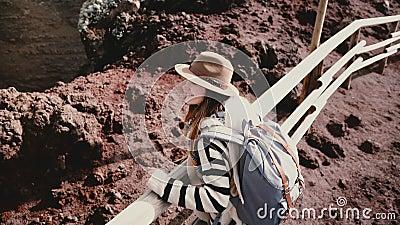 Opinião de ângulo alto o turista fêmea feliz novo com a trouxa e os braços largamente abertos na borda da cratera do vulcão do Ve video estoque