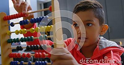 Opinião dianteira a estudante asiática que resolve o problema de matemática com o ábaco na mesa em uma sala de aula na escola 4k filme