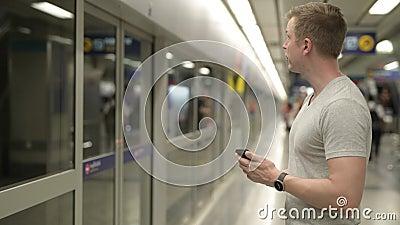Opinião do perfil o homem novo do turista que usa o telefone ao esperar o trem em Banguecoque vídeos de arquivo
