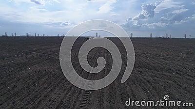 Opinião do zangão no solo marrom arado e no céu bonito, maquinaria agrícola em arar o campo video estoque