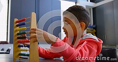 Opinião lateral a estudante asiática que resolve o problema de matemática com o ábaco na mesa em uma sala de aula na escola 4k video estoque