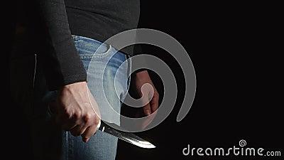 A opinião lateral o homem do perigo com uma faca vem no quadro e move-se sobre vídeos de arquivo