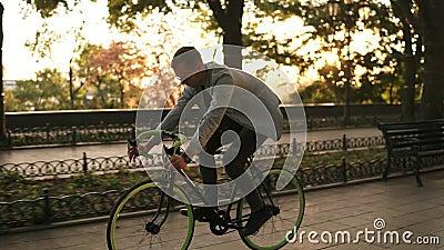 Opinião lateral um homem de sorriso novo nos óculos de sol que dão um ciclo uma bicicleta no parque ou no bulevar da manhã Movime filme