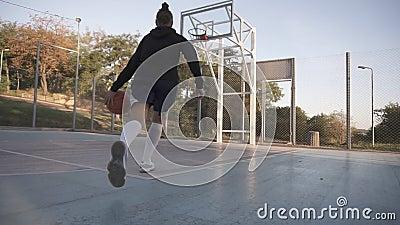 Opinião rara um jogador de basquetebol da moça que treina e que exercita fora na corte local Pingar com a bola video estoque