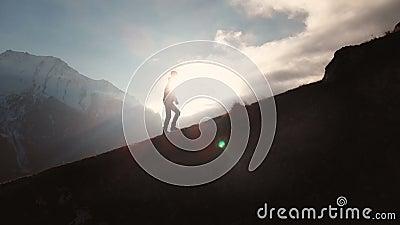 Opinión aérea de la misma posibilidad muy remota del tiro épico de un hombre que camina al borde de la montaña como silueta en un almacen de video