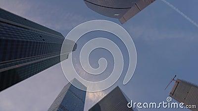 Opinión de parte inferior de los rascacielos con el movimiento del capítulo de la rotación de la parte inferior a rematar y detrá almacen de video