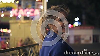 Opinión trasera la mujer atractiva joven con la cola de caballo que camina en parque de atracciones en la noche, dando vuelta alr almacen de video