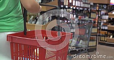 Opinión trasera la mujer con la cesta en tienda almacen de metraje de vídeo